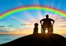 Disabled person in a wheelchair next to his dog Stock Images