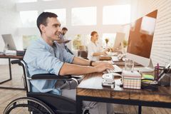 Disabled person in the wheelchair works in the office at the computer. He is smiling and passionate about the workflow Royalty Free Stock Images