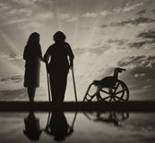 Disabled persons on crutches in reflection and nurse. Disabled persons woman on crutches in reflection and nurse helps her. Concept of disability Stock Photography