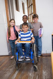 Disabled pupil with his friends in classroom Stock Images