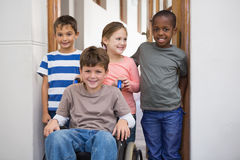 Disabled pupil with his friends in classroom Stock Image