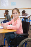 Disabled pupil smiling at camera in classroom Royalty Free Stock Photos
