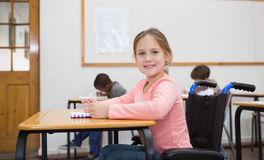 Disabled pupil smiling at camera in classroom Royalty Free Stock Photography