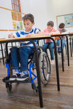 Disabled pupil writing at desk in classroom Stock Photography