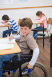 Disabled pupil writing at desk in classroom Stock Image