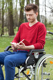 Disabled reading a book in garden Royalty Free Stock Photography