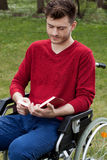 Disabled reading a book outdoors Stock Image