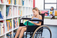 Disabled school girl reading book in library Stock Image