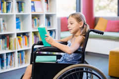 Disabled school girl reading book in library Stock Images