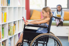 Disabled school girl selecting a book from bookshelf in library Stock Images