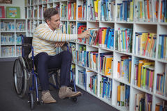 Disabled school teacher selecting book in library Stock Photos