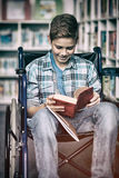 Disabled schoolboy reading book in library. At school royalty free illustration