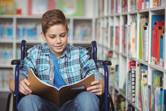 Disabled schoolboy reading book in library. At school Stock Image