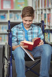 Disabled schoolboy reading book in library Royalty Free Stock Photo