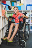 Disabled schoolboy selecting a book from bookshelf in library Stock Photo