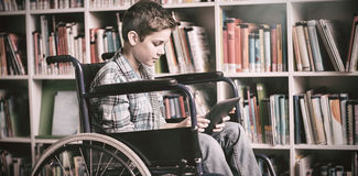 Disabled schoolboy using digital tablet in library Royalty Free Stock Image