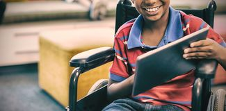 Disabled schoolboy on wheelchair using digital tablet in library stock photo