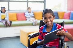 Disabled schoolboy on wheelchair using digital tablet in library. Portrait of disabled schoolboy on wheelchair using digital tablet in library at school Royalty Free Stock Image