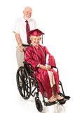 Disabled Senior Graduate and Spouse. Senior couple.  The husband is pushing his wife in a wheelchair.  She just graduated college.  Full body isolated on white Royalty Free Stock Photo