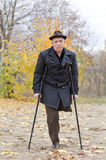 Disabled senior man on crutches. Determined to continue to enjoy a healthy active lifestyle enjoying a walk in an autumn park in his coat and hat Stock Photos
