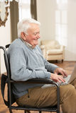 Disabled Senior Man Sitting In Wheelchair. Using Laptop Stock Photography