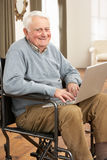 Disabled Senior Man Sitting In Wheelchair. Using Laptop Royalty Free Stock Images