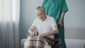 Disabled senior man sitting in wheelchair, male nurse supporting patient Stock Photos