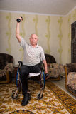 Disabled senior men doing exercises with dumbbells. Disabled senior man doing exercises with dumbbells in his hands like a part of rehabilitation at home in his Stock Photos