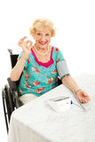 Disabled Senior Monitors Her Blood Pressure. Disabled senior woman in wheelchair taking her own blood pressure at home and giving the okay sign. White background stock image