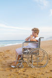 Disabled senior woman on beach Stock Images