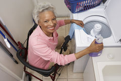 Disabled Senior Woman Doing Laundry At Home. Portrait of a disabled African American woman sitting on wheel chair by washing machine Stock Photo