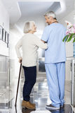 Disabled Senior Woman Holding Cane While Looking At Physiotherap Stock Images