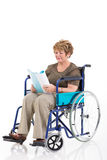 Disabled senior woman reading. A book on wheelchair isolated on white background Stock Image