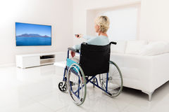 Disabled senior woman watching tv. In the living room at home Royalty Free Stock Images
