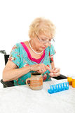 Disabled Senior Examining Her Medication. Disabled senior woman in wheelchair counting her pills into a pill container for the week.  White background Royalty Free Stock Photo