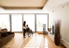 Disabled senior woman in wheelchair with her young daugher. Stock Photo