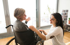Disabled senior woman in wheelchair with her young daugher. Royalty Free Stock Photography