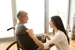 Disabled senior woman in wheelchair with her young daugher. Royalty Free Stock Photos