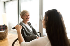 Disabled senior woman in wheelchair with her young daugher. Royalty Free Stock Images