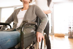 Disabled senior woman in wheelchair with her young daugher. Stock Photos