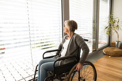 Disabled senior woman in wheelchair at home in living room. Disabled senior woman in wheelchair at home in her living room, looking out the window Royalty Free Stock Images