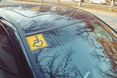 Disabled sign on the car glass. Stock Photos