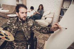 Disabled Soldier In Wheelchair Draws A Picture. After War Concept. Camouflage Uniform. Paralyzed Man With A Tassel. Home Relaxing. Return From Army. Family royalty free stock image