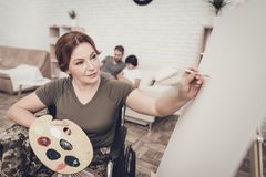Disabled Soldier In Wheelchair Draws A Picture. After War Concept. Camouflage Uniform. Paralyzed Woman With Tassel. Home Leisure. Return From Army. Family royalty free stock photography