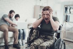 Disabled Soldier In Wheelchair. Suffer From Pain. Meeting After War. Son And Husband Background. Camouflage Uniform. Family Concept. Paralyzed Soldier. Home stock image