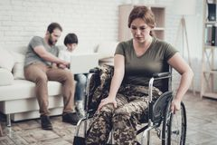 Disabled Soldier In Wheelchair. Suffer From Pain. Meeting After War. Son And Husband Background. Camouflage Uniform. Family Concept. Paralyzed Soldier. Home stock photo