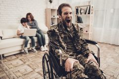 Disabled Soldier In Wheelchair. Suffer From Pain. Disabled Soldier In Wheelchair. Suffering From Pain. Meeting After War. Son And Wife Background. Camouflage stock photo