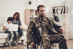Disabled Soldier In Wheelchair. Suffer From Pain. Disabled Soldier In Wheelchair. Suffering From Pain. Meeting After War. Son And Wife Background. Camouflage stock image
