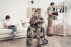 Disabled Soldier Woman In Wheelchair Book Reading. Meeting After War. Son And Husband. Camouflage Uniform. Family Concept. Paralyzed Soldier. Home Lifestyle stock photography