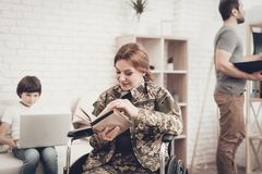 Disabled Soldier Woman In Wheelchair Book Reading. Meeting After War. Son And Husband. Camouflage Uniform. Family Concept. Paralyzed Soldier. Home Lifestyle royalty free stock photo